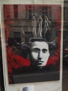 """L'opera è un ritratto in bianco e nero di Antonio Gramsci con la sua distintiva e folta capigliatura, su uno sfondo rosso che fa riferimento al comunismo ed evoca la violenza dell'epoca. In cima alla chioma, rispetto a una folla, possiamo riconoscere tre figure in evidenza, una citazione de """"Il quarto Stato"""" (1901) di G. Pellizza da Volpedo che rappresentò pittoricamente la popolazione più svantaggiata, la stessa a cui Antonio Gramsci dedicò un'intera vita con le sue lotte."""